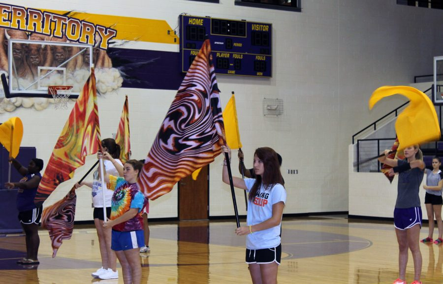 Color+Guard+members+Jamie+Phillips%2C+Emmelee+Weathers+and+Morgan+Altom+hold+their+flags+while+Belle+Jessica+Kaiser+gives+hers+a+twirl.+The+Belles+and+color+guard+members+worked+together+during+summer+practices+on+routines.+The+two+groups+and+the+band+are+working+together+on+a+new+style+of+halftime+performance.