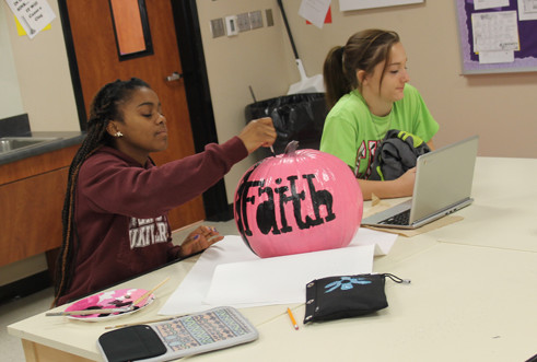 Freshman Jordan Jenkins works on her pumpkin for the Pink Out game.