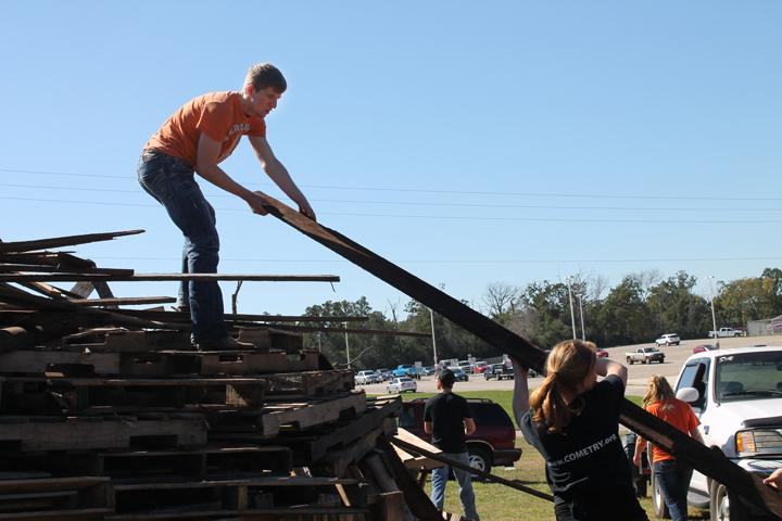 Senior Jacob Davis helps to life wood high up onto the stack.