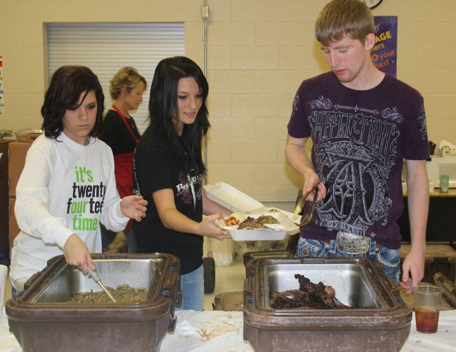 Seniors Chelsea Brewer, Morgan Altom and Jacob Davis serve the steak dinners at last week's fundraiser. The senior class came away with more than $12,000 to use on graduation night.
