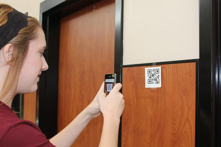 Junior+Macey+Jonas+whips+out+her+cell+phone+to+check+out+the+QR+code+posted+in+the+hallway+for+the+Spanish+class+project.+TEacher+Valerie+del+Bosque+used+the+codes+to+help+her+students+learn+vocabulary.+