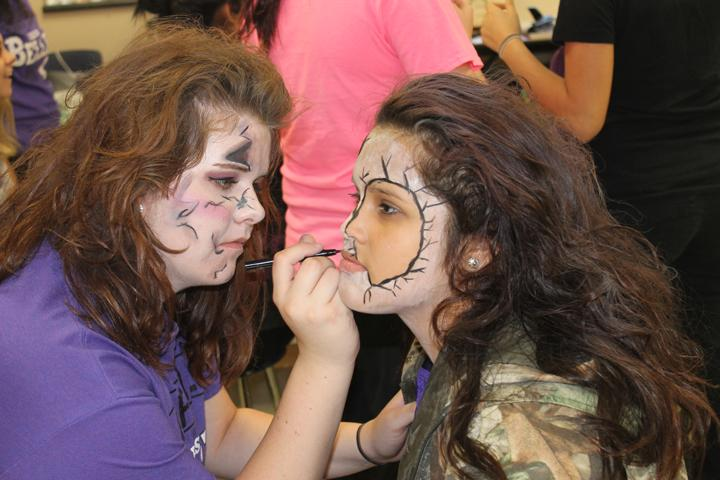 Sophomore Brooke Barron decorates Maria Maltos's face for the Belle's performance at the junior high pep rally. The girls danced as broken dolls.