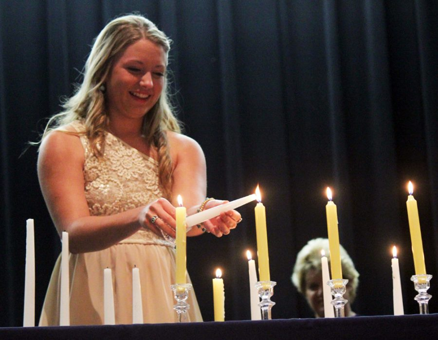 Sophomore Jacie Jones lights a candle during the NHS induction of new members. Jacie was one of the inductees.