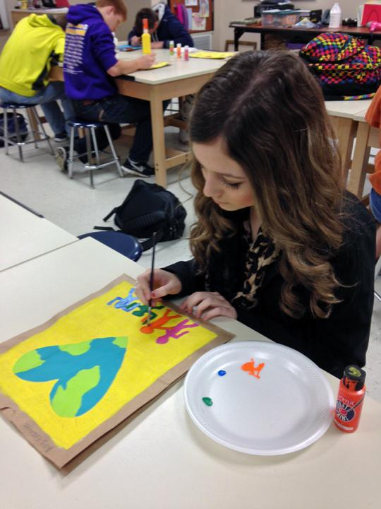 Sophomore Ally Gaskins works on her bag for art class. The students used acrylic paints on brown paper bags to complete the projects.