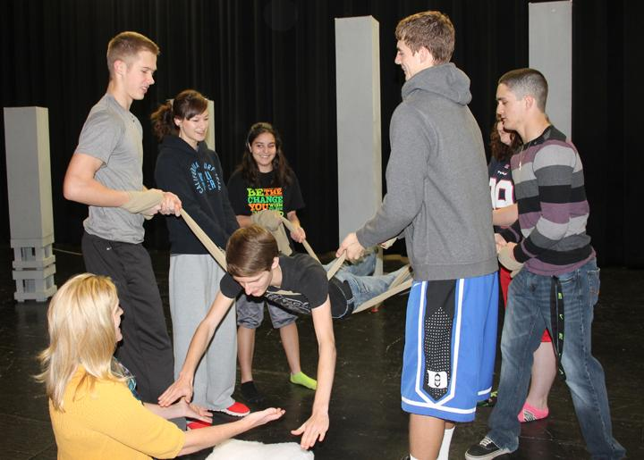 Director Jill Henson and cast members work on practicing their new Commedia techniques, which they plan to use in the OAP this year. Senior Preston Mosley is practicing his falls.