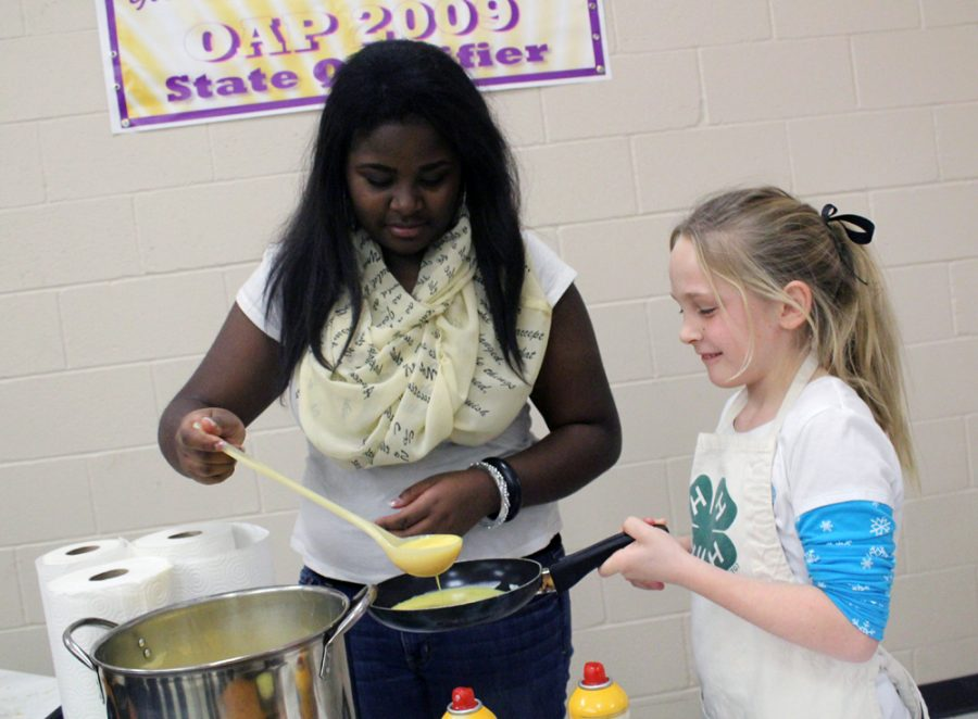 Junior Adrian Randle helps third grader Dannie Young start an omelet. 4-H members of all ages cook the omelets to order for customers. It is one of two food-related fundraisers for the year, along with the fried pies the club sells at the Buffalo Stampede.