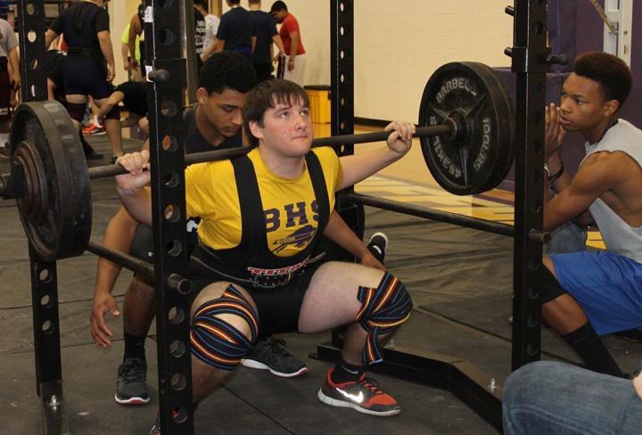 Sophomore+Clint+Guyton+gets+set+to+lift+with+senior+JJ+Kolb+and+junior+Josheph+Thompson+spotting+him.