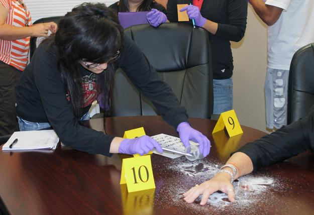 Senior+Marisol+Lopez+collects+evidence+from+the+powdery+substance+spilled+around+victim+Janet+Slaughter.+