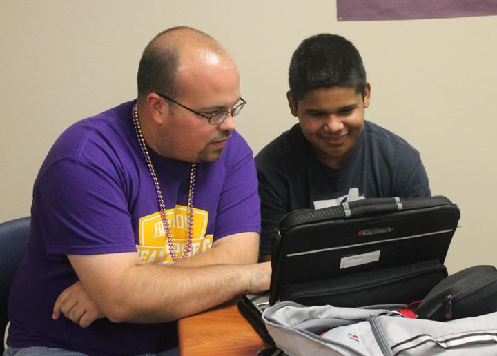 Teacher Mitchell Pate works with students Luis Esquivel.
