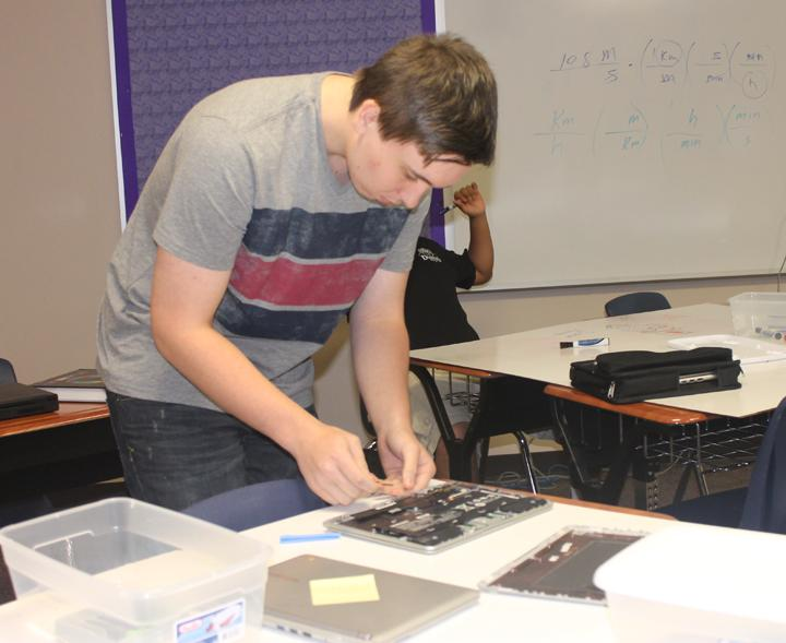 Senior Clay LaCour works on a Chromebook during PC repair class. Students work with teacher Kyle Gleghorn to gain practical, hands-on experience in repairing technology around campus.