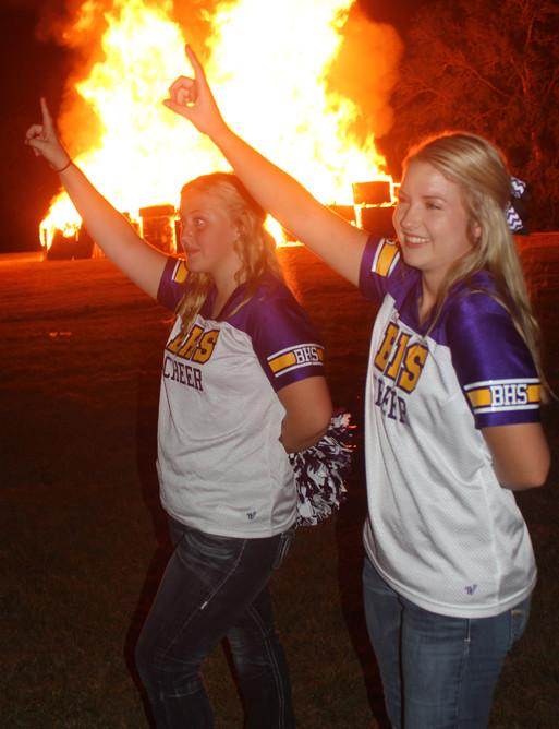 Senior Haley Martin and junior Jacie Jones join in the singing of the school song during bonfire.