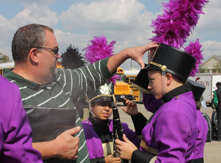 Director Jeff Villarreal helps the band members adjust uniforms before heading onto the field to compete. The contest was held at the University of Mary Hardin-Baylor.