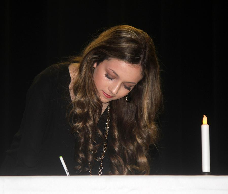Sophomore Ally Gaskins signs the membership book during the NHS induction.
