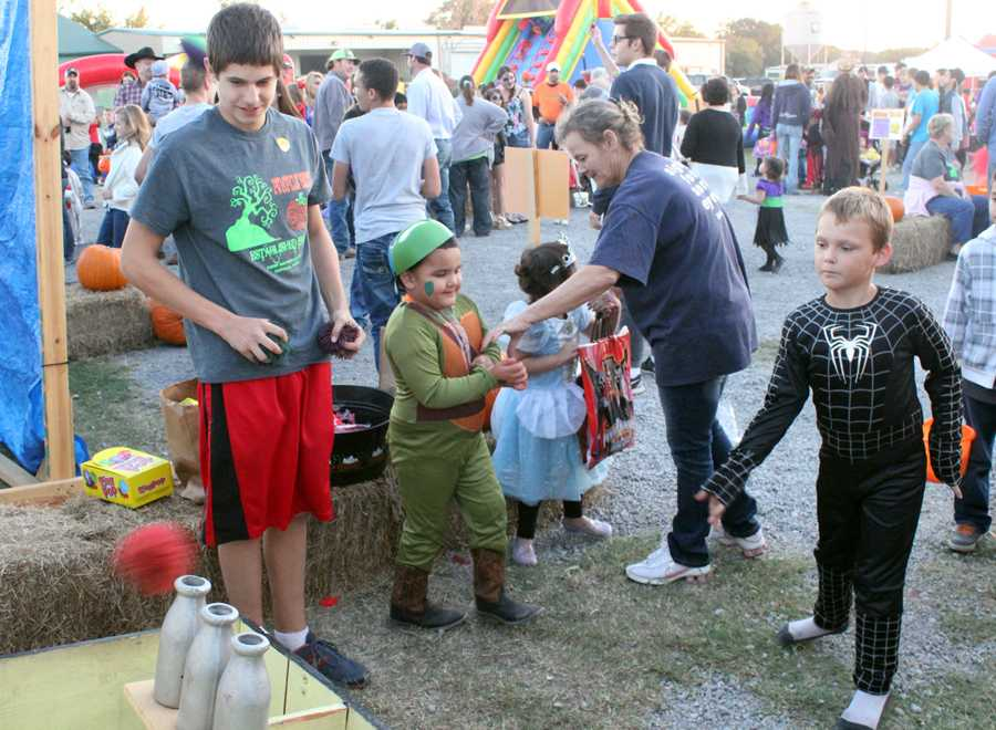 Sophomore Evan Grisham works a game booth at Pumpkin Patch at First Baptist Church.