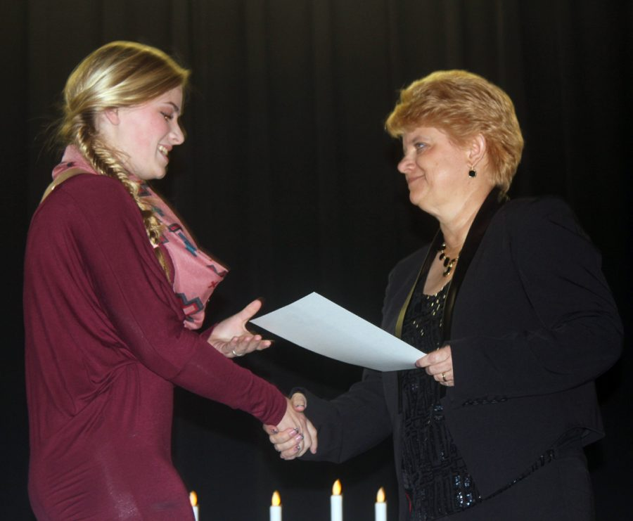 Sophomore+Kysa+Taylor+accepts+her+certificate+from+principal+Tracy+Gleghorn+during+the+induction+ceremony+Monday+night.