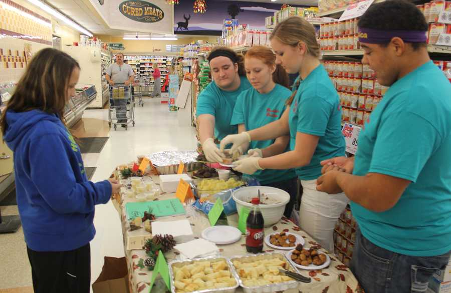 FCCLA+members+Brittany+Scott%2C+Jessica+Devore%2C+Kassidy+Bell+and+Chris+Jennings+work+a+booth+at+Taste+of+the+Holidays+at+Brookshire+Bros.+