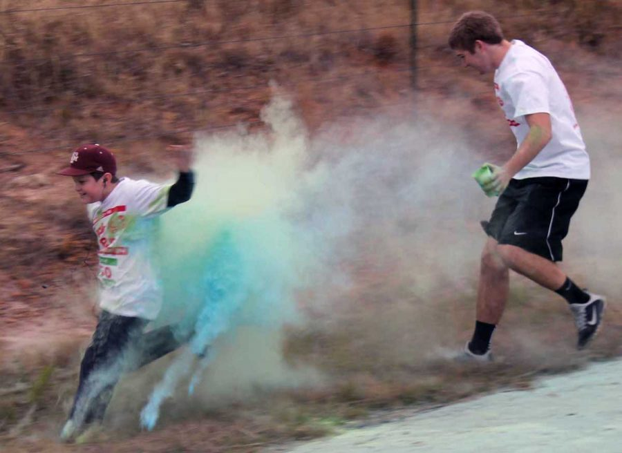 Junior+Logan+Freeman+chases+a+young+runner+off+the+road+to+hit+him+with+color+powder+during+the+4-H+Jingle+Bell+Color+Run+last+weekend.+