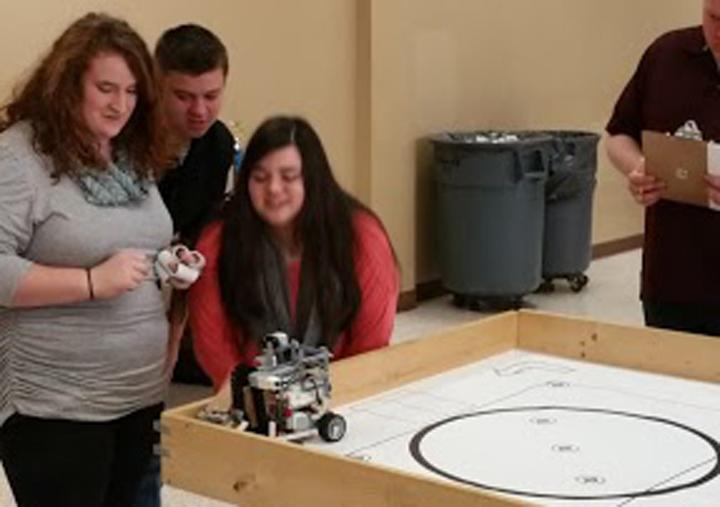 Robotics+members+Brittany+Scott%2C+Cody+Pilkington+and+Kaiden+Loep+watch+nervously+as+their+robot+runs+the+course+at+area+competition.+