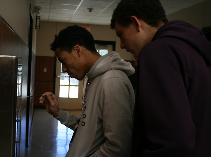 Seniors OT Garcia and Roy Kuykendall check the hallway for fingerprints while they search for Sully, the science department lizard.