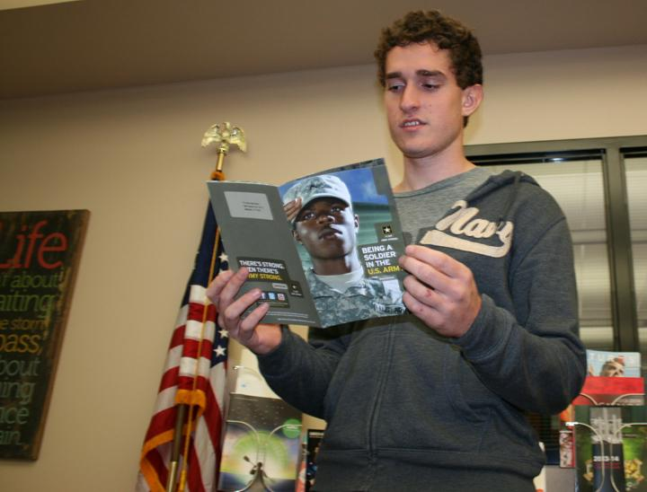 Junior Nathanael Young checks out a flyer on entering the military in the library. Young hopes to go into the army after high school.