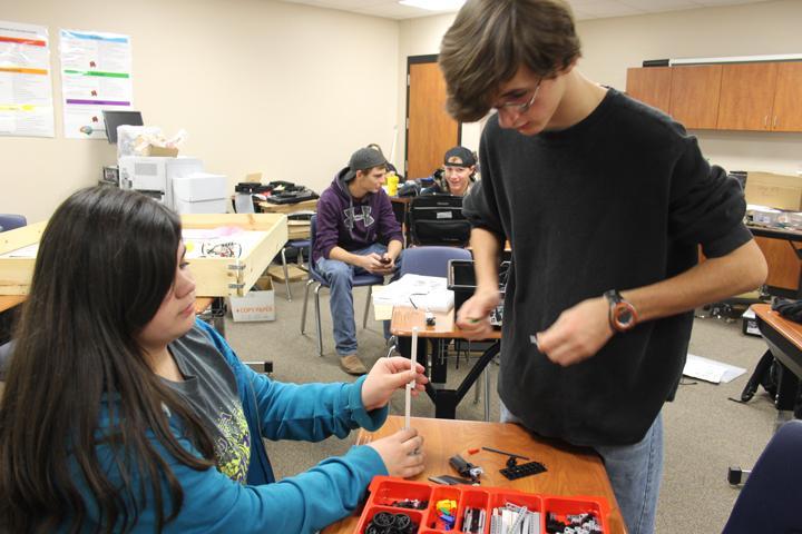 Freshmen Kaiden Loep and Garrett McAlpine work on their robot in coach Kyle Gleghorn's room.