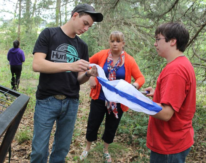 Forensics students Roy Kuykendall and Austin Melton study insects they caught in a net at the site of the dead pig while teacher Patrice Cox looks on. The class went out every day for a couple of weeks to examine the pig.