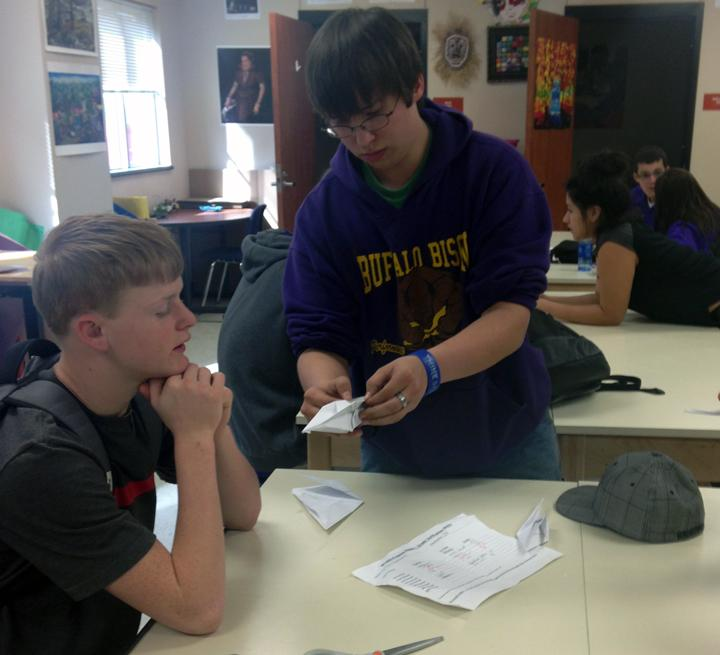 Junior Austin Melton shows sophomore Dillon Beshears how to make a paper swan in art class.