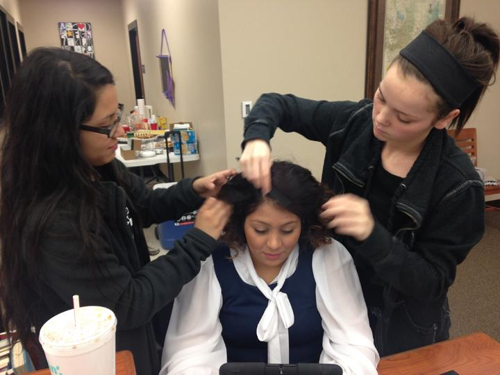 Crew+members+Karina+Sotelo+and+Taryn+Morman+work+on+hair+and+makeup+for+junior+Brittnie+Garcia.