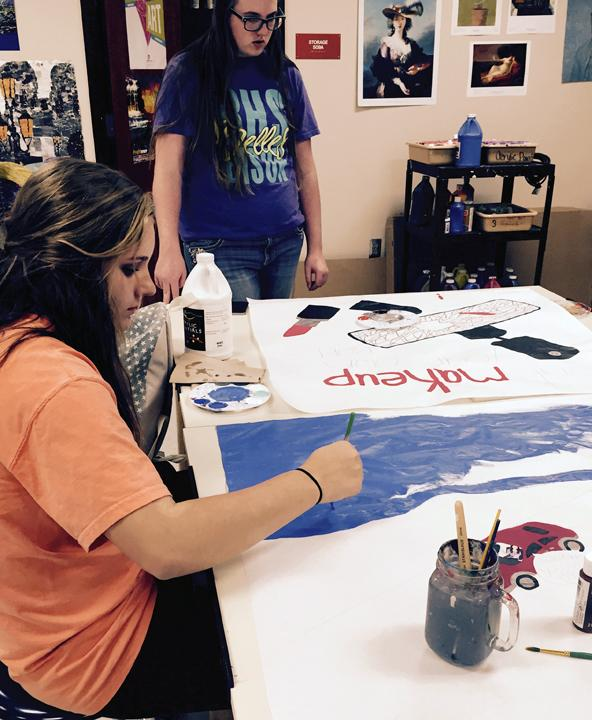 Sophomore Kassidy Bell works on her poster in art class.