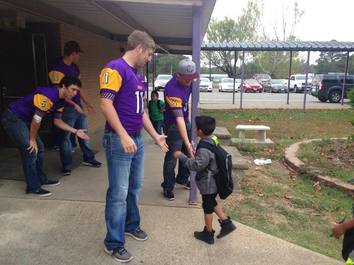 Football players Logan Freeman, Trey Minter and Bryce Pauler greet an elementary student as he gets to the cafeteria.