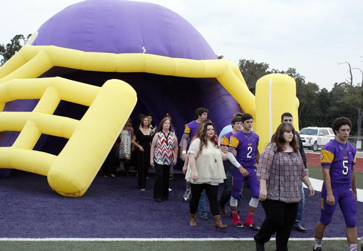 Parents+and+seniors+head+out+of+the+giant+helmet+and+onto+the+field+during+senior+walk.
