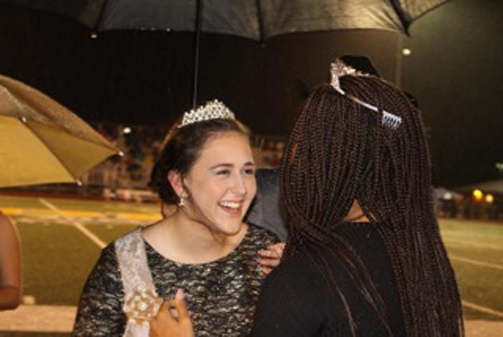 Senior+Allison+Grissett+laughs+with+last+year%27s+homecoming+queen+Erykah+Anderson+as+Anderson+congratulates+Grissett+on+becoming+the+2015+queen.+The+rain+kept+everyone+under+umbrellas+for+the+crowning.