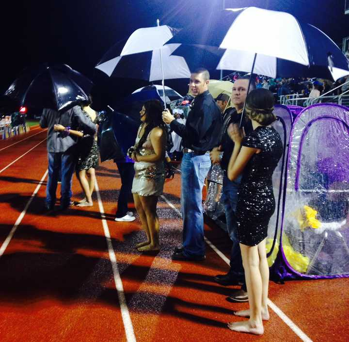 The homecoming queen candidates and their escorts use umbrellas to try to stay dry as they wait for halftime to start.