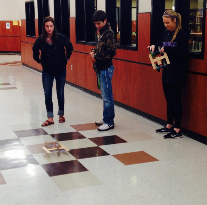Physics students Gracie Ferguson and Hannah Eakin practice with their mouse trap cars while classmate Shelley Pate watches.