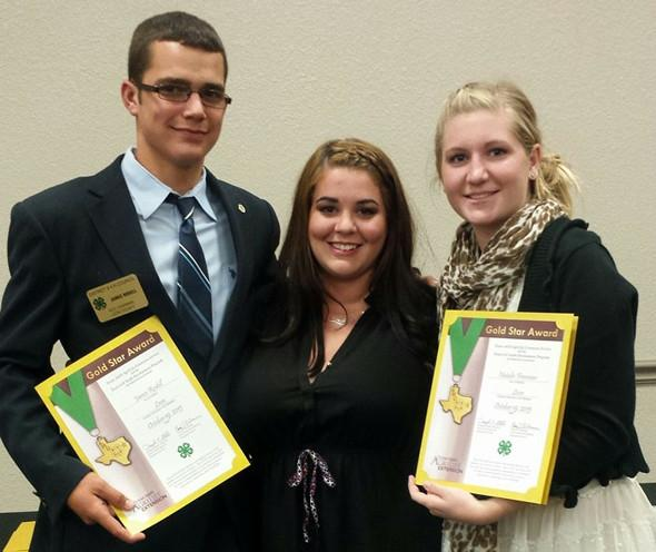 4-H students James Rodell and Natalie Freeman show off their District Gold Stars with Leon County Extension Agent Amanda Shortt.