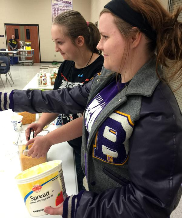 Seniors Jaylee Hullum and Sarah Burchfield help customers load up their baked potatoes at the fundraiser. All profits went to the ProGrad fund.