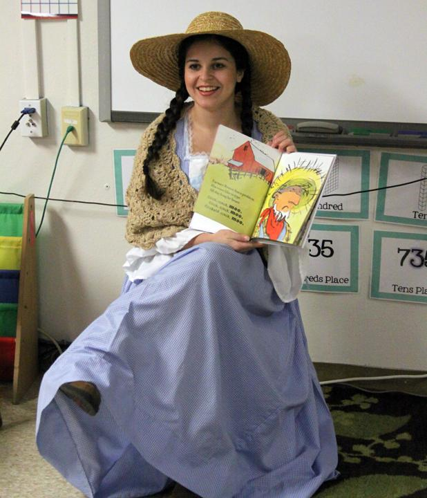 Senior Kendall Morales reads from Click, Clack, Moo while dressed as Farmer Brown's wife.