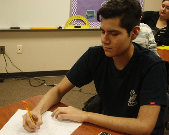 Oscar Lopez works on homework during activity period.