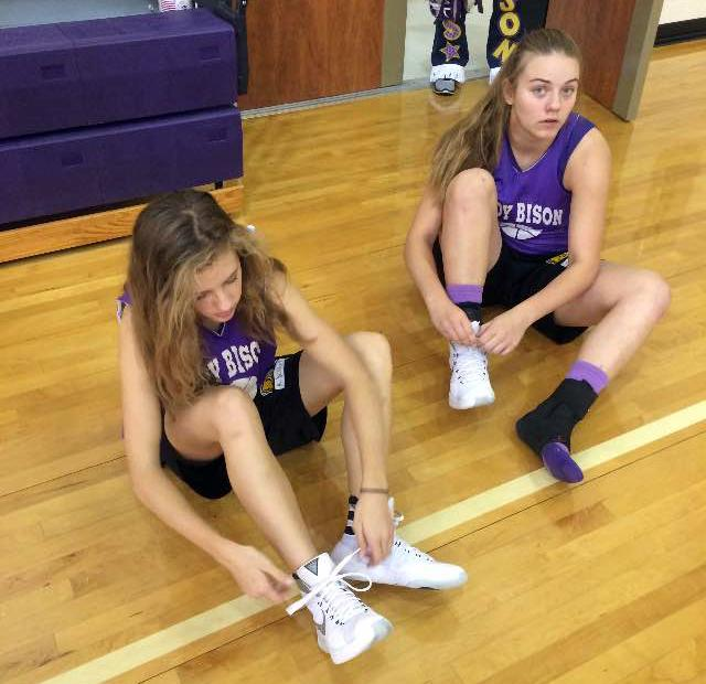 Freshmen Mollie Dittmar and Andrea Daniel lace up before hitting the court.