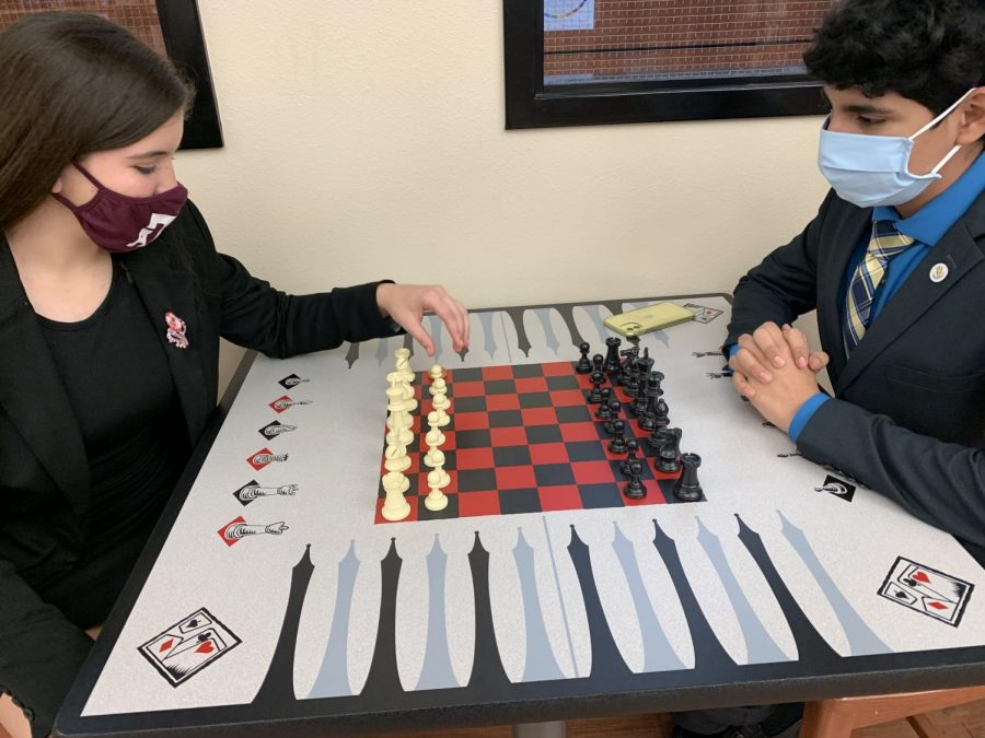 Freshman Nicollette Arabie and junior Omar Almeida play checkers during a break between rounds of CX debate at a Saturday practice meet.