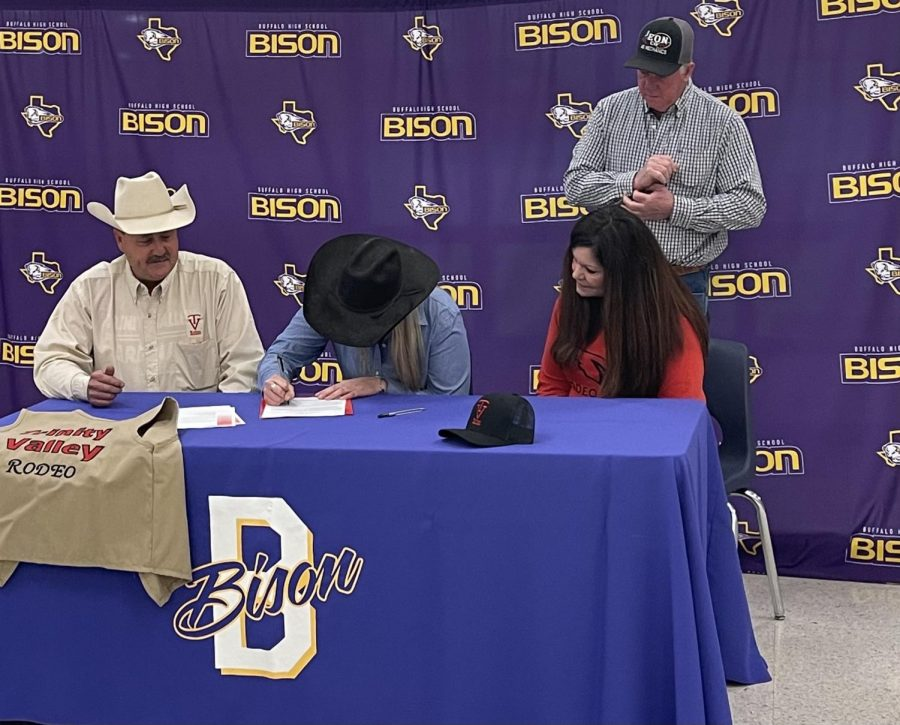 Senior Katy Webb signs with TVCC to rodeo while her future coach and her parents look on. She was the fourth senior to sign to compete in college.