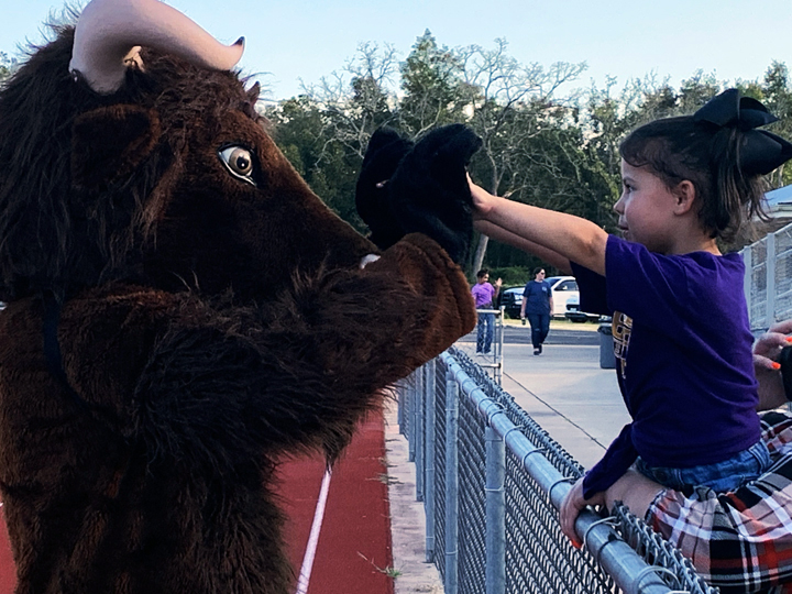 A young fan greets Bucky at the junior varsity game against Teague.