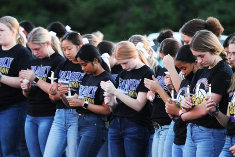 Students and staff are joined by community members at a candlelight memorial for teacher Lori Brigner, who passed away after battling COVID.