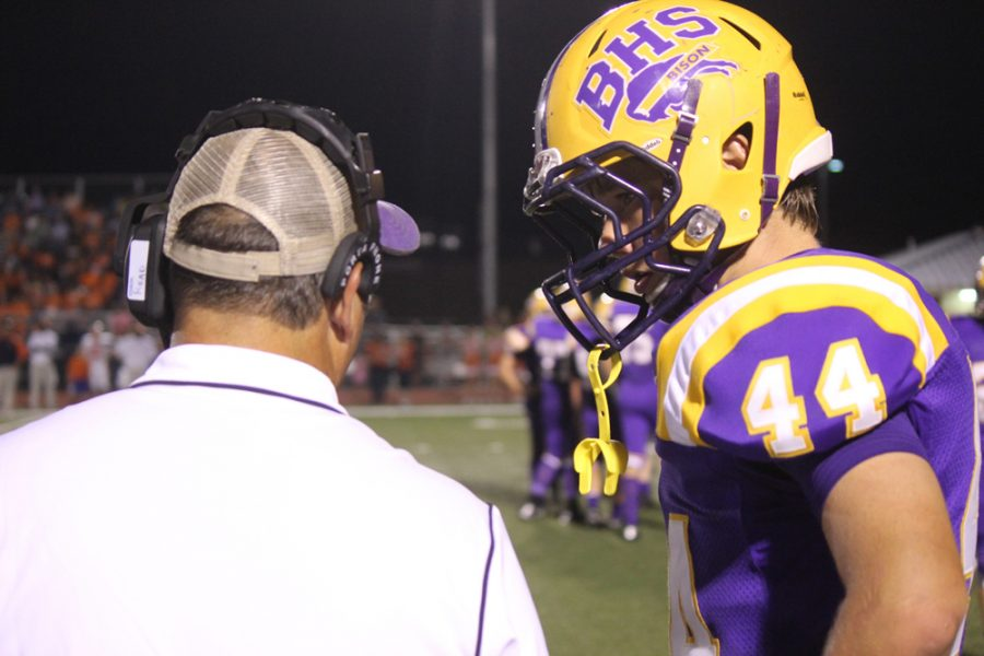 Freshman+Rhett+Read+listens+to+instructions+from+dad+and+head+coach+Mark+Read.+