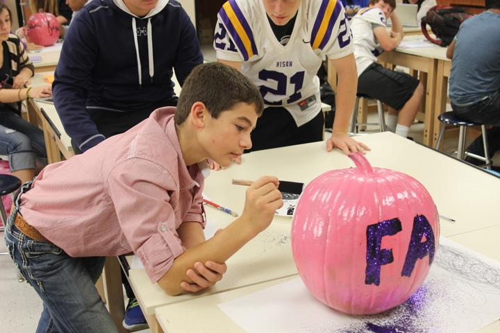 Freshman+Shelley+Pate+works+on+his+pink+pumpkin+-+one+of+dozens+painted+by+art+students+to+decorate+the+field+at+the+Pink+Out+game.+