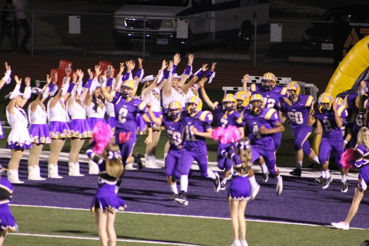 The+cheerleaders+sport+pink+poms+while+the+football+players+fun+through+the+victory+line+at+Friday+night%27s+Pink+Out+game.