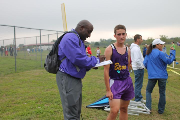 Sophomore+Nathanial+Young+checks+in+with+coach+Pat+Roberts+during+the+district+cross+country+meet+at+Blooming+Grove.+The+meet+continued+despite+rain+throughout+the+day.