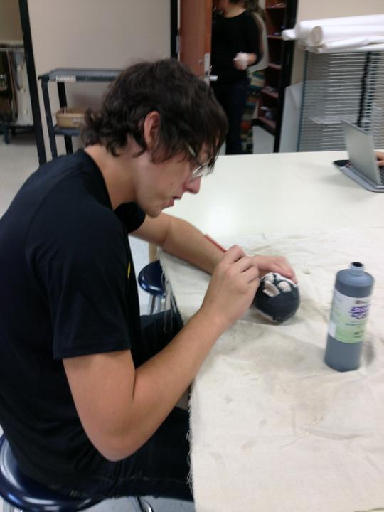 Senior+Ryan+Slatter+works+on+adding+color+details+to+his+Angry+Bird+using+ceramic+glaze.+The+class+created+owl+sculptures+after+their+Angry+Birds.+