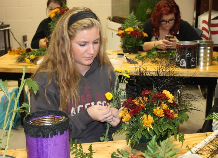 Freshman+Natalie+Freeman+decides+which+flowers+to+put+where+on+her+first+arrangement.+This+was+the+first+year+for+the+floral+design+class.