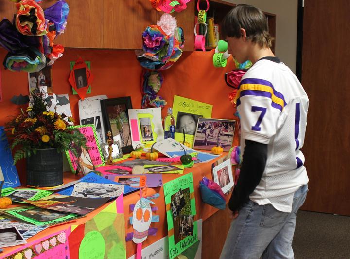 Sophomore+Bryce+Fulmer+looks+at+the+display+that+students+put+together+for+their+Dia+de+los+Muertos+celebration+in+Spanish+class.
